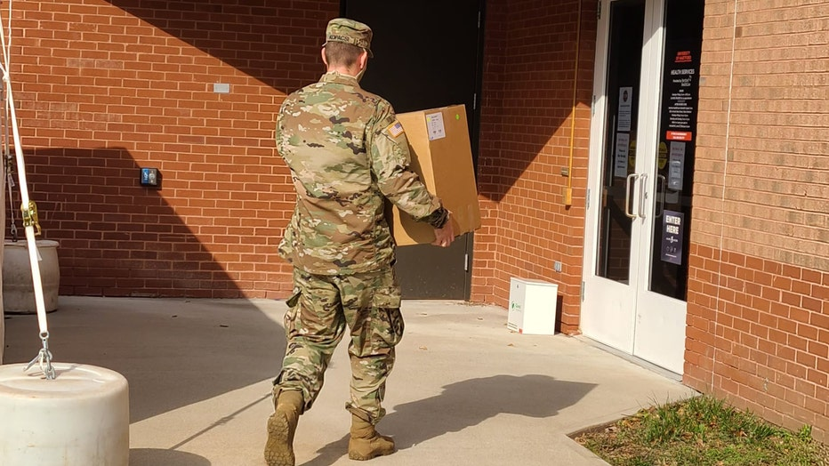 Military member in camo carries a box towards the door of a clinic