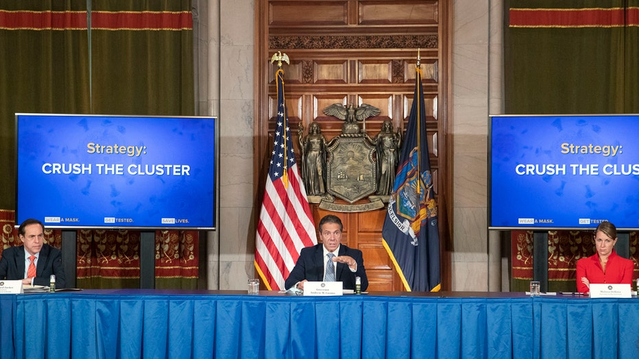 Cuomo and two others sit behind a long table with flags and screens behind them