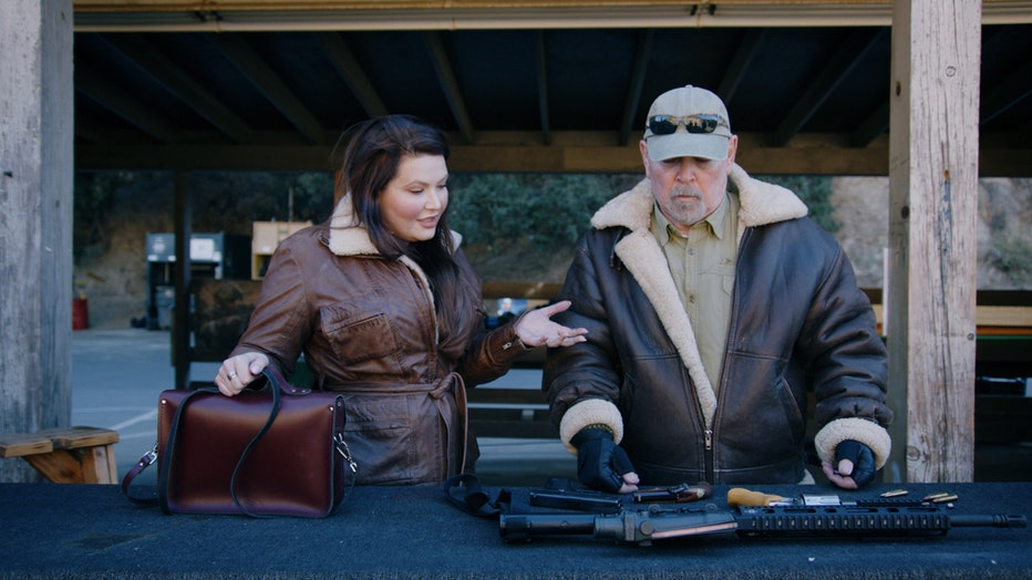 Two people standing over a table of firearms