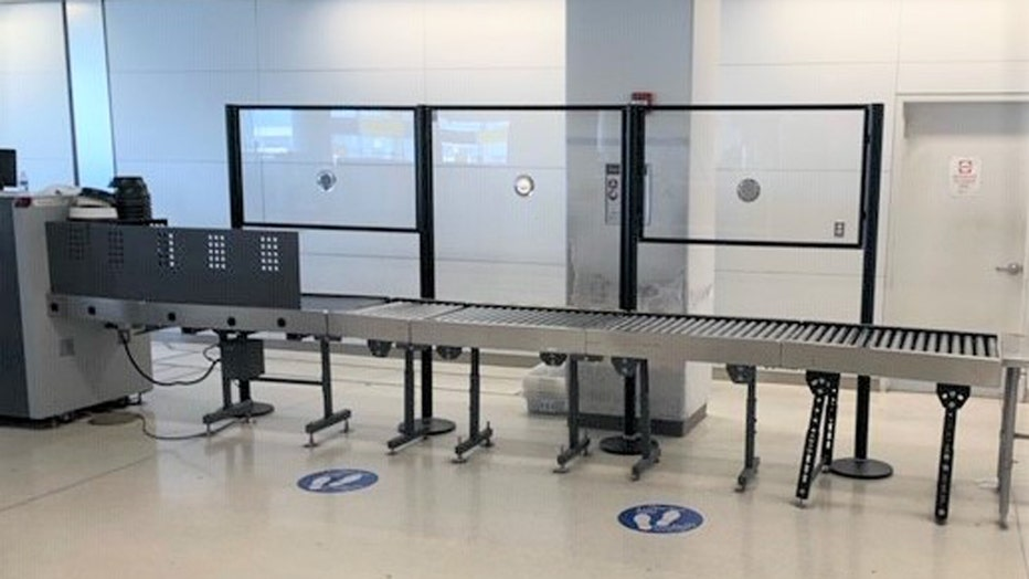Acrylic barriers on one side of a baggage conveyor belt