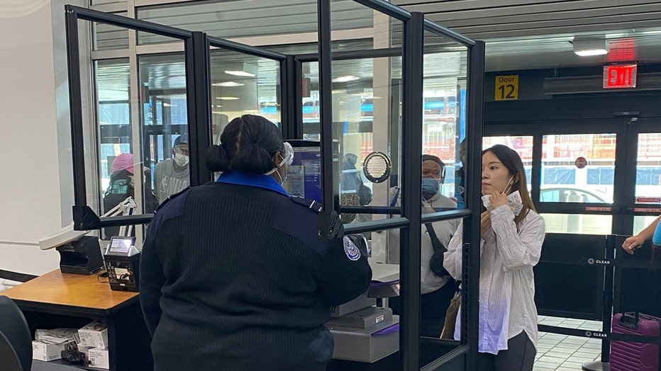 Clear acrylic barriers around a TSA officer's checkpoint