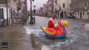 Santa paddles down flooded Venice street