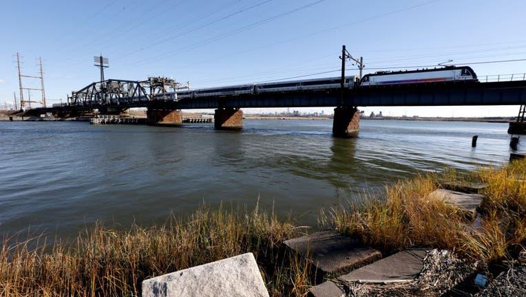 A New Jersey Transit train rides across a portal bridge
