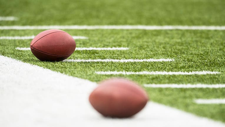 Footballs rest on the sideline before a game.