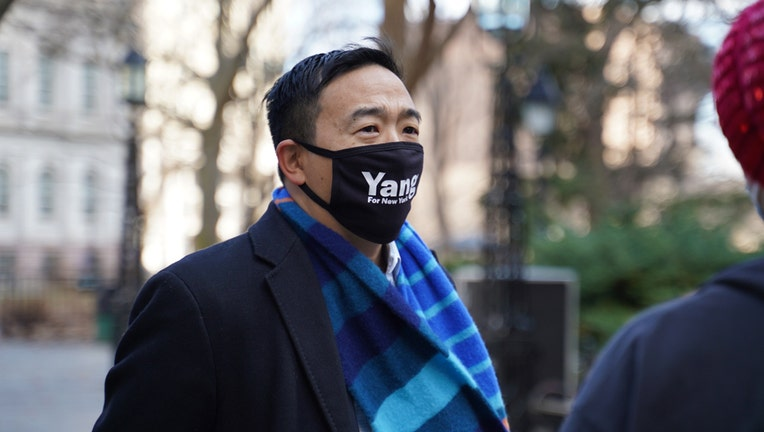 Andrew Yang wearing a black coat, blue patterned scarf, and black face mask with the word 'Yang', standing outdoors with City Hall in background