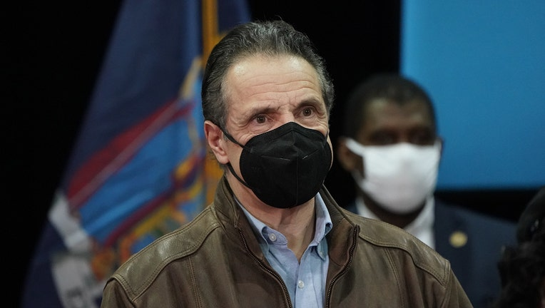 Andrew Cuomo wearing a black mask, light blue shirt, and brown leather jacket