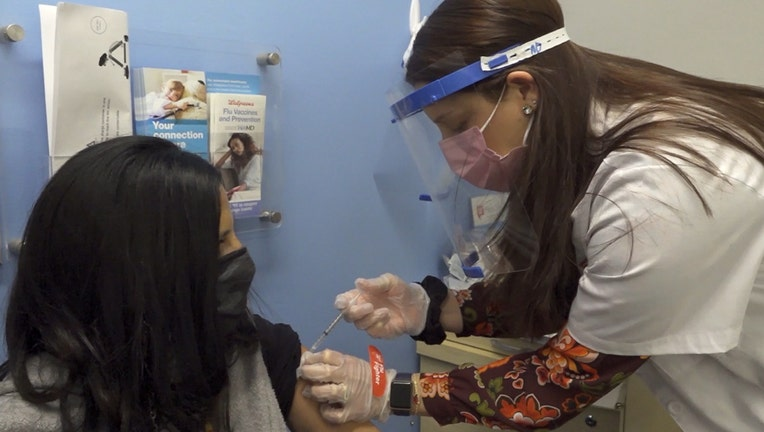 Tech wearing mask and shield gives an injection to a woman wearing a mask