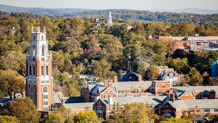 Aerial view of Yale University campus with many green trees, red brick tower and buildings and hills in the distance