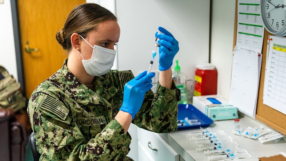Navy medic in camo and a mask prepares a syringe