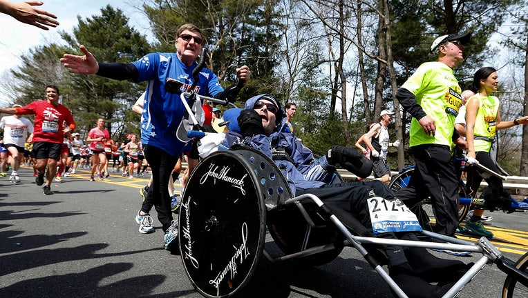 An athlete in a blue shirt and sunglasses holds out his hand for a high-five as he pushes his son in a special racing wheelchair. They are among dozens of runners on a tree-lined road in the Boston Marathon on a sunny day.