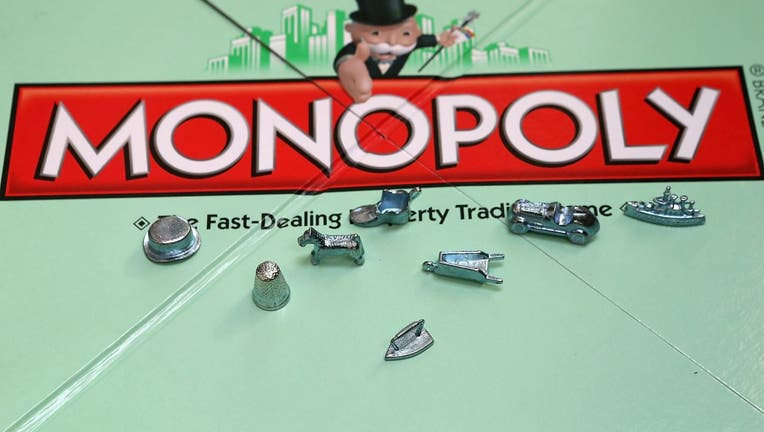 In this photo illustration, Monopoly game pieces are displayed