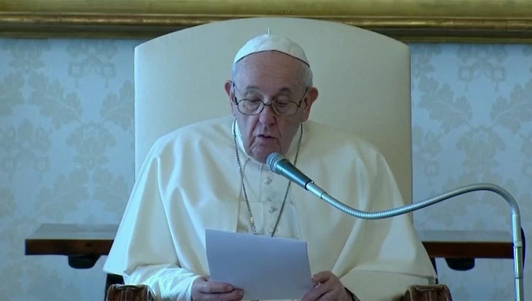 Pope Francis wearing white skullcap and vestments and glasses holds a document and speaks into a microphone