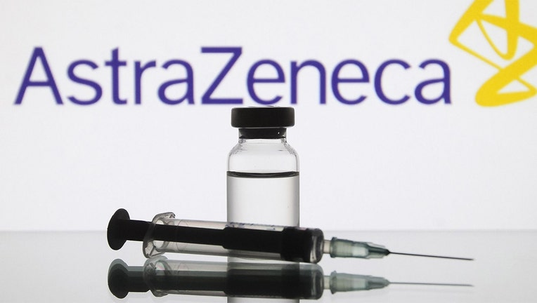 A medical syringe and a vial in front of the AstraZeneca British biopharmaceutical company logo.(Photo by STR/NurPhoto via Getty Images)