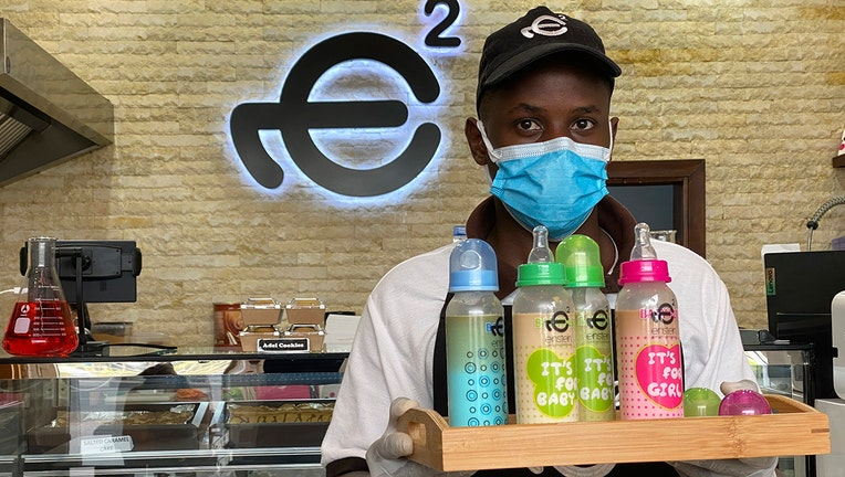 A waiter poses with a tray of baby bottles that he brought out from storage, at Einstein Cafe in Dubai, United Arab Emirates, Sunday, March 14, 2021. (AP Photo/Kamran Jebreili)