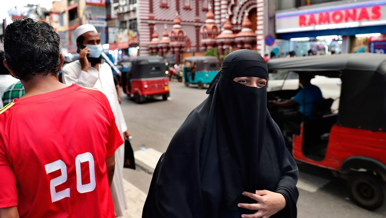 A burqa clad Sri Lankan Muslim woman walks in a street of Colombo, Sri Lanka, Saturday, March 13, 2021. Sri Lanka on Saturday announced plans to ban the wearing of burqas and said it would close more than 1,000 Islamic schools known as madrassas, citing national security. (AP Photo/Eranga Jayawardena)
