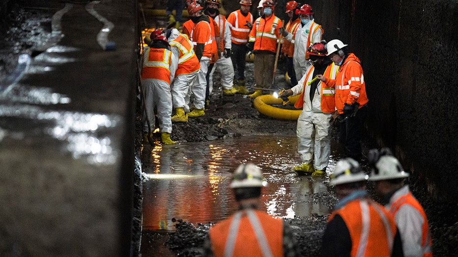 More than a dozen workers in hard hats and safety gear work inside a partially flooded rail tunnel; two workers shine flashlights at the ground