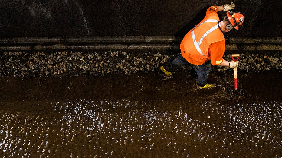 View from above of a worker in orange safty gear testing a flooded rail bed in a tunnel