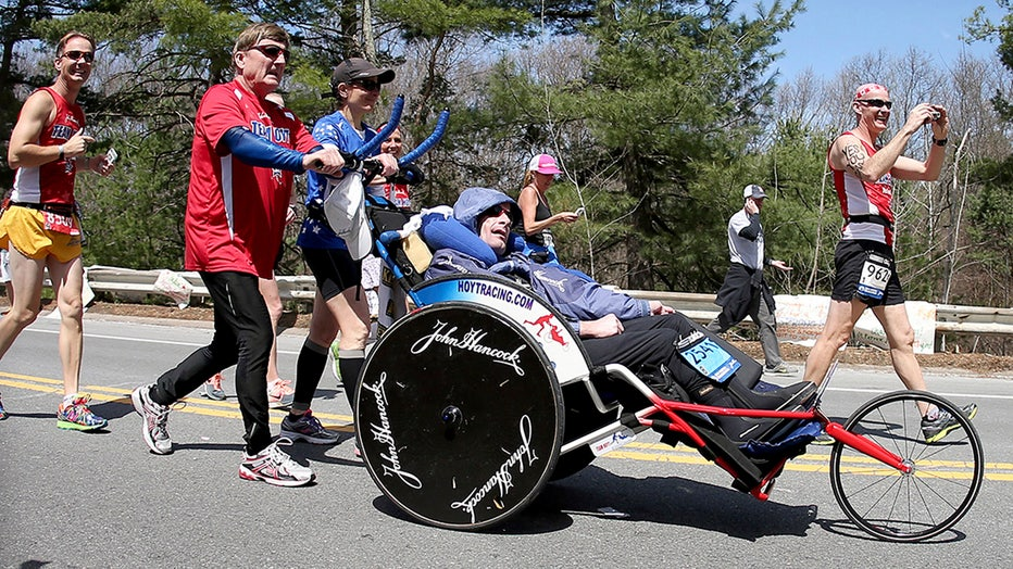 A man in a red shirt, black track pants and sunglasses pushes his son in a racing wheelchair along a suburban road during the Boston Marathon. Several runners are around them.