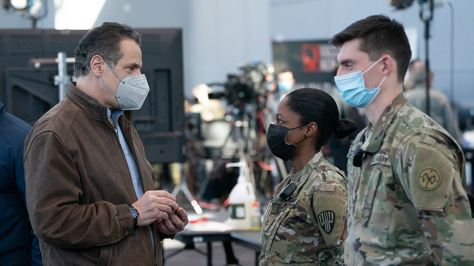Cuomo wearing mask and brown jacket speaks to two service members wearing masks and camouflage uniforms