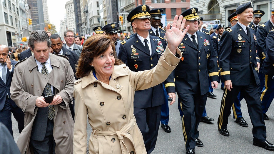 Kathy Hochul in a tan trench coat smiles and waves as she marches in front of uniformed soldiers