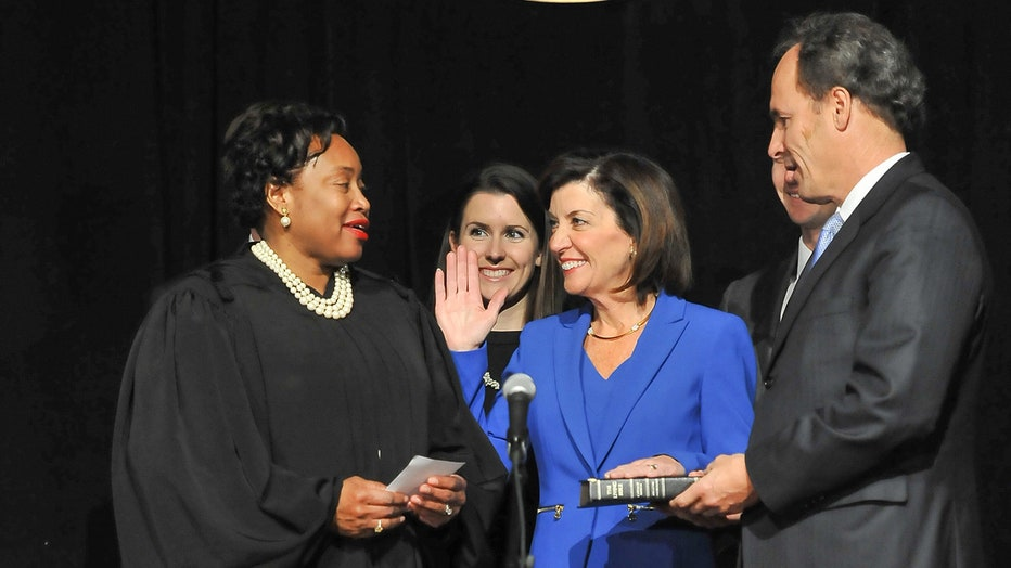 A smiling Kathy Hochul in a blue suit holds right hand up and left hand on a bible as judge administers the oath of office; a man stands to her left and a woman stands behind her