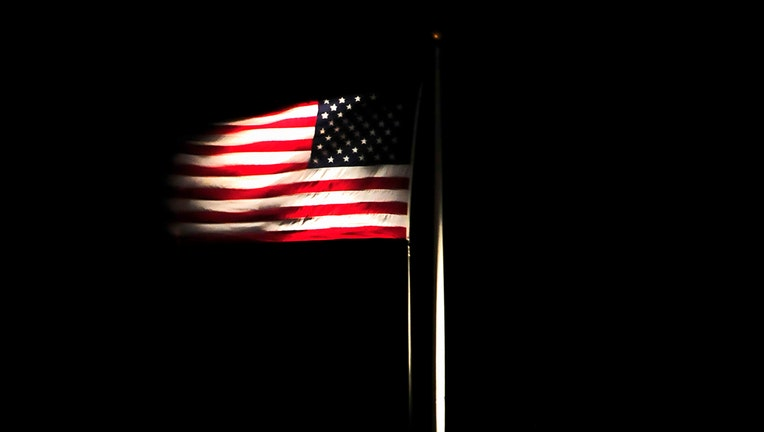 An illuminated American flag waves at night