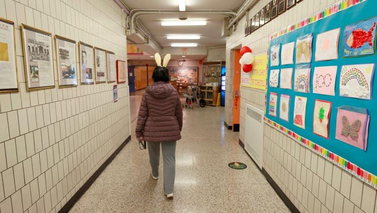 Principal Alice Hom walks through a hallway