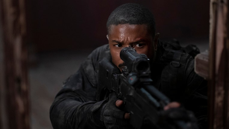 Actor Michael B. Jordan looks into a scope while he aims a rifle