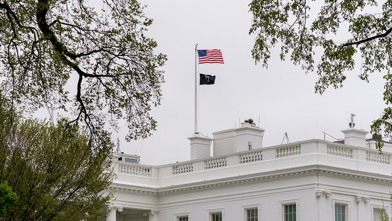 A POW/MIA flag, symbolizing America's Missing in Action and Prisoners of War, flies along with the American flag above the White House, Friday, April 9, 2021, in Washington. (AP Photo/Andrew Harnik)