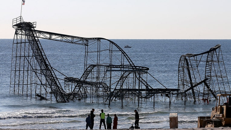 Workers prepare to remove the Star Jet roller coaster that has been in the ocean for six months after the Casino Pier is sat on collapsed when Superstorm Sandy hit, May 14, 2013 in Seaside Heights, New Jersey. The Casino Pier has contracted Weeks Marine to remove the Jet Star roller coaster from the Atlantic Ocean. (Photo by Mark Wilson/Getty Images)