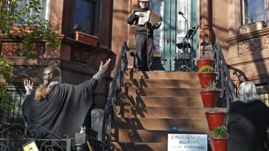 In this Wednesday, April 15, 2020 photo, choir director and neighbor Pam McAllister, left, encourages musician Paul Stein, center, to invent timely words to his songs as Stein entertains neighbors with an accordion concert from his stoop in front of his Sunset Park, Brooklyn home during the coronavirus outbreak in New York.