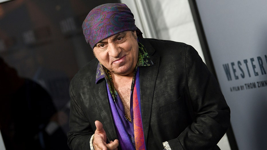 Actor and musician Steven Van Zandt wearing a black sports coat and colorful shirt and head covering