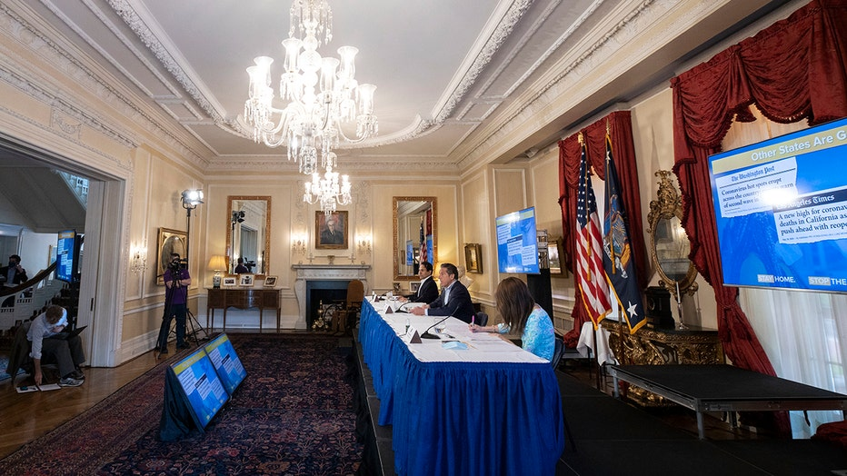 Gov. Cuomo and aides sit behind a long table in a large room in the governor's mansion; an ornate chandelier hangs from the ceiling; US and New York flags are against the right wall