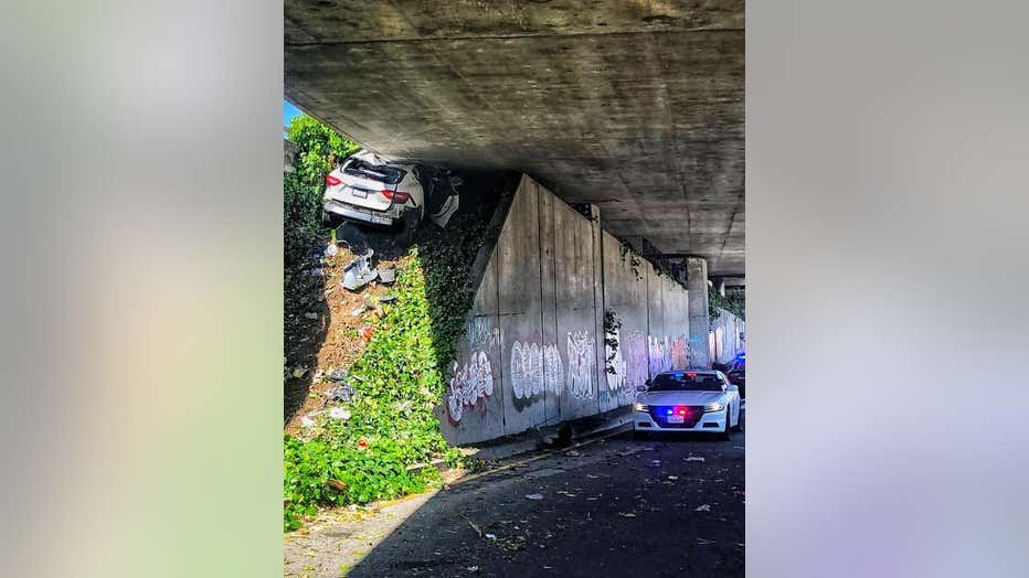 This photo provided by the California Highway Patrol shows the scene where a man fleeing from the CHP totaled his girlfriend's Maserati SUV after he careened up an embankment and slammed into the underside of an overpass, wedging the car under a freeway in Oakland, Calif., on Monday, April 12, 2021. (California Highway Patrol