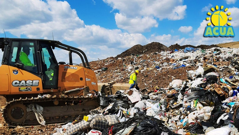 Heavy equipment and workers search a huge pile of trash at a landfill