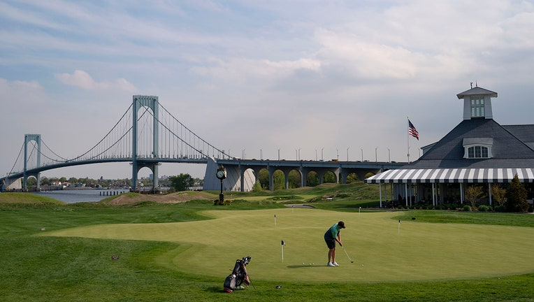 Patrons practice on the putting green beside the clubhouse as the Whitestone Bridge looms in the distance at Trump Golf Links at Ferry Point in the Bronx