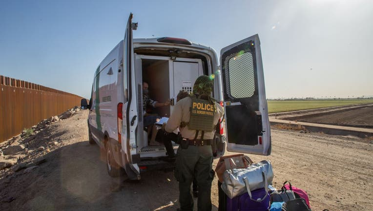 A family of asylum seekers from Colombia boards the Border Patrol Inmate transport