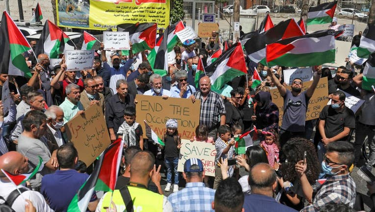 Palestinians demonstrate in the city of Ramallah, in the occupied West Bank, in solidarity with Gaza on May 18, 2021. (Photo by ABBAS MOMANI/AFP via Getty Images)