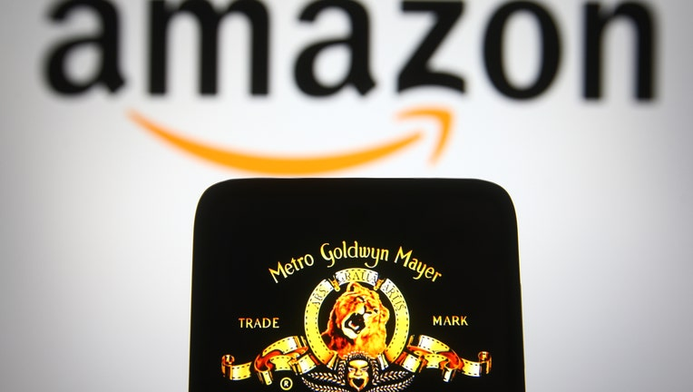 The MGM logo is seen on a smartphone screen with an Amazon logo in the background.