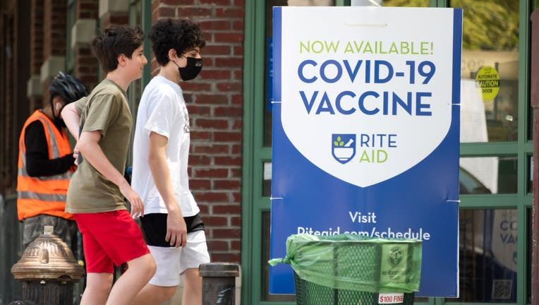 """People walk by a sign that reads, """"Now available! COVID-19 vaccine"""" in TriBeCa"""