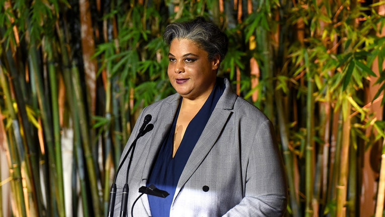 Author Roxane Gay wearing a gray and blue outfit speaks into a microphone; behind here are large bamboo trees