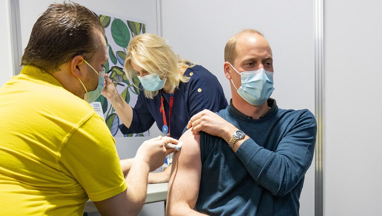 A medical worker gives a vaccine injection to Prince William while another medical worker stands behind the prince; Prince William wears a light blue mask and a bluw long-sleeved shirt