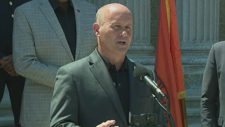 Police Commissioner Patrick Ryder wearing a gray suit speaks into a microphone outdoors