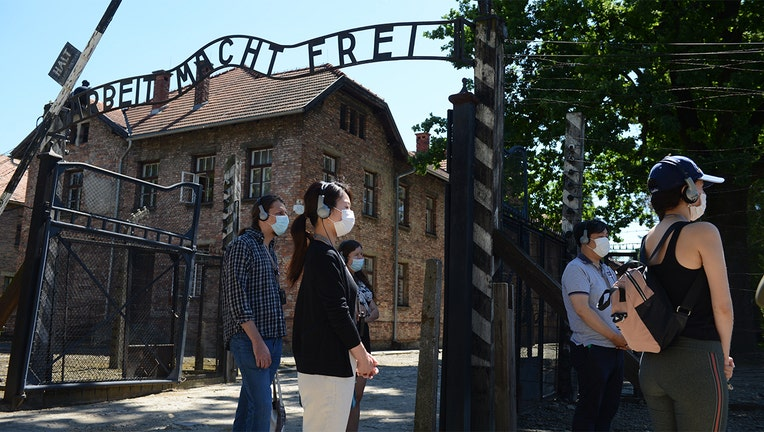 """Visitors are seen near the gate with its inscription """"Work sets you free"""" as the memorial site of the former German Nazi death camp Auschwitz in Oswiecim.(Photo by BARTOSZ SIEDLIK/AFP via Getty Images)"""