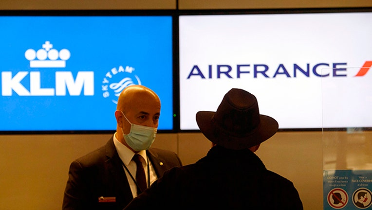 An employee wears a face mask as a passenger checks-in for a flight at a Air France and KLM counter.(File Photo by PATRICK T. FALLON/AFP via Getty Images)