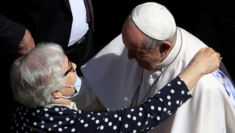 Pope Francis hugs Lidia Maksymowicz, a Polish survivor to Auschwitz, as he leaves the Courtyard of St Damasus at the end of his weekly General Audience on May 26, 2021 in Vatican City. (Photo by Franco Origlia/Getty Images)