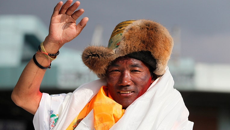In this May 20, 2018, file photo, Nepalese veteran Sherpa guide, Kami Rita waves as he arrives in Kathmandu, Nepal. Rita, 51, an ace Sherpa guide scaled Mount Everest Friday for the 25th time breaking his own record for the most successful ascents of the world's highest peak. (AP Photo/Niranjan Shrestha, File)