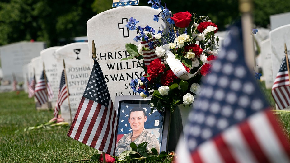 Flowers, flags and a framed photo decorate a soldier's headstone at Arlington National Cemetery