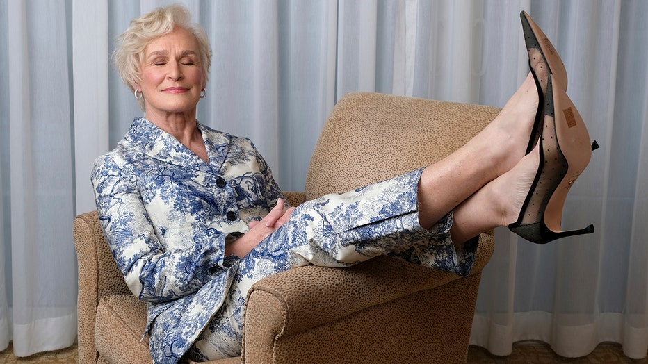 Actress Glenn Close, with her eyes closed and feet raised, sits in an armchair; she wears a white and blue patterned suit