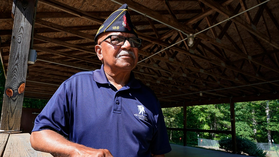 Army veteran wearing a garrison cap and navy blue polo stands under a wooden patio roof